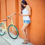 Sexy asian woman standing near the wall and vintage bicycle Royalty Free Stock Images