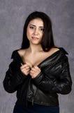 Sexy asiatische Frau mit den bloßen Schultern, welche die Lederjacke und schwarzen Rock aufwerfen auf einem grauen Hintergrund tr Stockfotografie
