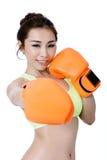Sexy asiatische junge Frauen nehmen den Sitz ab, der orange Handschuhverpacken auf wh trägt Lizenzfreies Stockbild