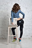 In black tights made of latex. Young woman with long hair. Beautiful girl with big booty in the pants of latex royalty free stock photo