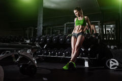 Sexy athlete girl lean on dumbbell row in gym Stock Photo