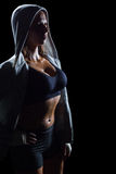 Sexy athlete in hood. Standing against black background Stock Photos