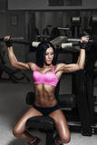 Sexy athlete woman lifts in the gym. Brunette performs an exerci Stock Photos