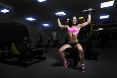 Sexy athlete woman lifts in the gym. Royalty Free Stock Image