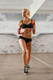 Sexy, athletic, blonde woman in the gym, against the background Royalty Free Stock Photos