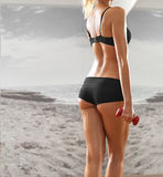 Sexy, athletic, blonde woman in the gym, against the background Royalty Free Stock Images