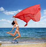 Sexy athletic brunette jumping on the beach. Royalty Free Stock Image
