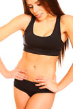 Sexy athletic girl looking at her belly on a white background Royalty Free Stock Image