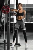 athletic girl working out in gym. Fitness woman doing exercise Stock Photography