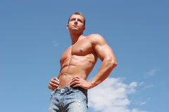 Sexy athletic male model in blue jeans Stock Photography