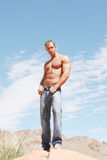 Sexy athletic male model in blue jeans Stock Images