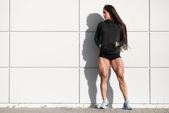 athletic woman with big quads. Muscular girl posing outdoor, muscular legs royalty free stock images