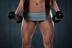 athletic woman showing muscular legs. Fitness girl with dumbbells Royalty Free Stock Images