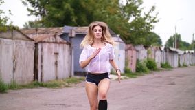 athletic young blond woman in shorts, performs various strength exercises with the help of tires, jumps. In summer stock video