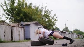 Athletic young blond woman in shorts, performs various strength exercises with the help of tires, push-ups, In. Athletic young blond woman in shorts, performs stock video footage
