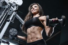 Sexy athletic young girl training arms in gym. Beautiful sexy athletic young caucasian girl working out training arms in the gym gaining weight pumping up Stock Photo