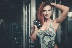 Sexy athletic young girl training arms in gym. Beautiful sexy athletic young caucasian girl working out training arms in the gym gaining weight pumping up Royalty Free Stock Images
