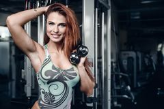 Sexy athletic young girl training arms in gym. Beautiful sexy athletic young caucasian girl working out training arms in the gym gaining weight pumping up Royalty Free Stock Photos