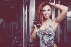 Sexy athletic young girl training arms in gym. Beautiful sexy athletic young caucasian girl working out training arms in the gym gaining weight pumping up Stock Image