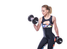 Sexy athletic young woman with perfect strong muscular body wearing sportswear tracksuit pumping up muscles with dumbbells. Stock Photography