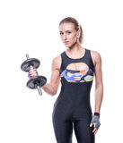 Sexy athletic young woman with perfect strong muscular body wearing sportswear tracksuit pumping up muscles with dumbbells. Royalty Free Stock Photography