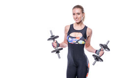 Sexy athletic young woman with perfect strong muscular body wearing sportswear tracksuit pumping up muscles with dumbbells. Royalty Free Stock Images
