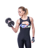 Sexy athletic young woman with perfect strong muscular body wearing sportswear tracksuit pumping up muscles with dumbbells. Stock Photos