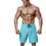 Sexy athletischer Mann, der die ABS des muskulösen Körpers und des sixpack, lokalisiert über weißem Hintergrund zeigt Starker Man Stockfotos