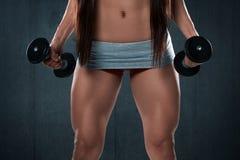 Sexy atletische vrouw die spierbenen tonen Het meisje van de geschiktheid met domoren Royalty-vrije Stock Afbeeldingen