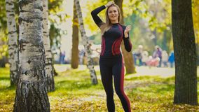 Sexy Attractive female blonde bikini-fitness model stretching in the autumn park on ground covered yellow leaves -  arms Stock Images
