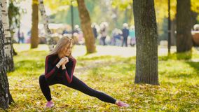 Sexy Attractive female blonde bikini-fitness model stretching in the autumn park on ground covered yellow leaves - legs flexibilit Royalty Free Stock Image