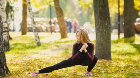 Sexy Attractive female blonde bikini-fitness model stretching in the autumn park on ground covered yellow leaves - legs flexibilit Royalty Free Stock Photos
