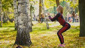 Sexy Attractive female blonde bikini-fitness model stretching in the autumn park on ground covered yellow leaves - sports squats Royalty Free Stock Photos