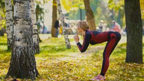 Sexy Attractive female blonde bikini-fitness model stretching in the autumn park on ground covered yellow leaves - the tilt of the Stock Photo