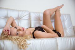 Sexy attractive girl lying on coach Royalty Free Stock Photos