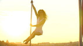attractive girl poledancer performs advanced pole dance tricks at sunset on portable dancing stage over the skyline