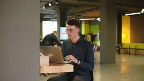 Sexy attractive male wearing glasses typing something on laptop. Working process in open co-working space. Slow motion. Footage stock video footage