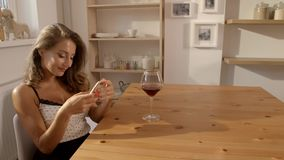 And attractive woman in candid dress sits at the table in a cafe with glass of red wine and texting on her. Video of the and attractive woman in candid dress stock footage