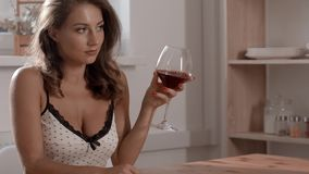 and attractive woman in candid dress is sitting in the cafe with glass of red wine in her hand and flirts with stock footage