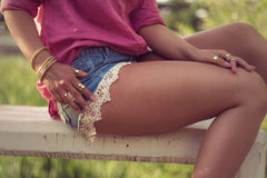 Sexy and attractive woman legs and hands, wearing sexy casual denim shorts. With macrame, lace attachment a pink shirt and her hands full of gold fashion Stock Photos