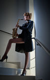 Sexy attractive woman with saxophone and long legs posing on stairs. Young attractive blonde playing sax. Musical instrument. Jazz Royalty Free Stock Photography