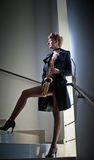Sexy attractive woman with saxophone and long legs posing on stairs. Young attractive blonde playing sax. Musical instrument. Jazz Royalty Free Stock Image
