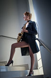 attractive woman with saxophone and long legs posing on stairs. Young attractive blonde playing sax. Musical instrument. Jazz Royalty Free Stock Photo