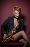 Sexy attractive woman with saxophone posing on red background. Young sensual blonde playing sax. Musical instrument, jazz Stock Photos