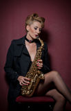 Sexy attractive woman with saxophone posing on red background. Young sensual blonde playing sax. Musical instrument, jazz Royalty Free Stock Photography