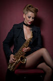 Sexy attractive woman with saxophone posing on red background. Young sensual blonde playing sax. Musical instrument, jazz Royalty Free Stock Images