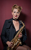 Sexy attractive woman with saxophone posing on red background. Young sensual blonde playing sax. Musical instrument, jazz Stock Photo