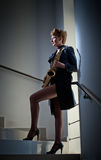 Sexy Attractive Woman With Saxophone And Long Legs Posing On Stairs. Young Attractive Blonde Playing Sax. Musical Instrument. Jazz