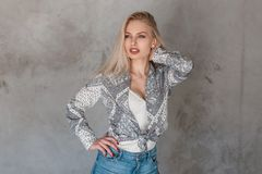 Sexy attractive young woman a blonde in a fashionable shirt with a pattern in a trendy t-shirt in stylish jeans in the studio. Near the vintage gray wall stock photography
