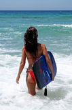 Sexy attractive young woman in red bikini walking out to blue sea on sunny beach with body board und Royalty Free Stock Photo